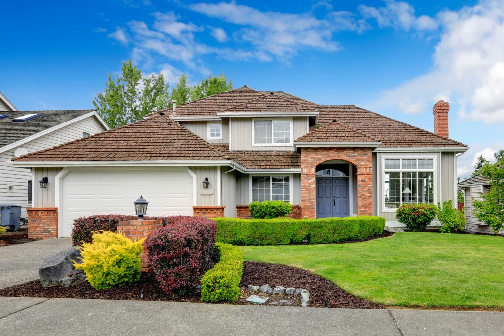 Classic house exterior with brick trimmed entrance porch, green lawn and trimmed hedges. Garage with driveway