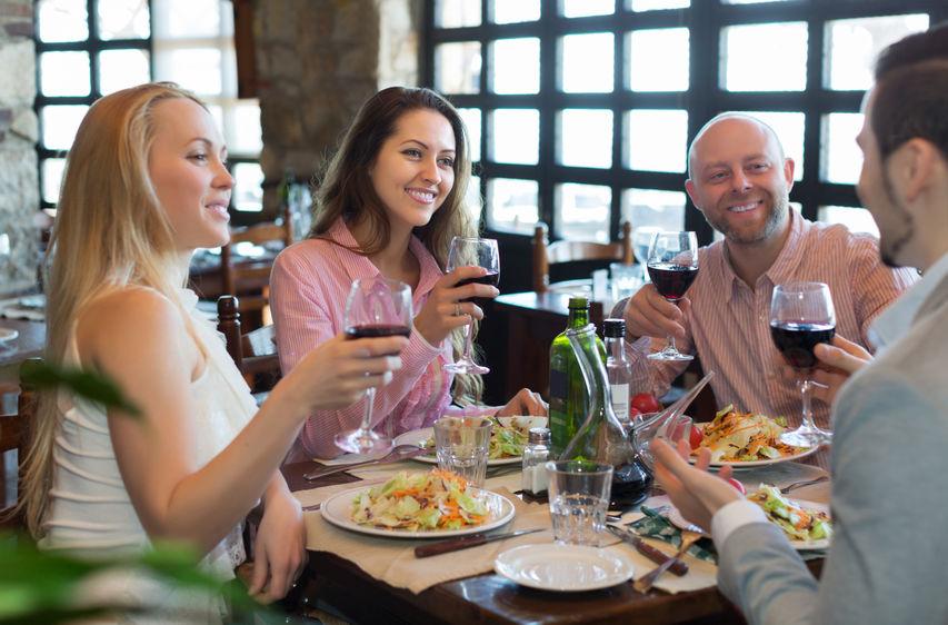 Portrait of smiling young adults having dinner in family restaurant. Focus on brunette girl